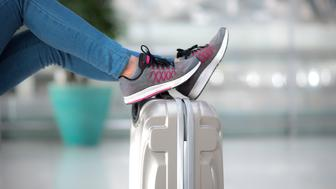 Cropped shot of passenger leg on luggage waiting for departure at the airport