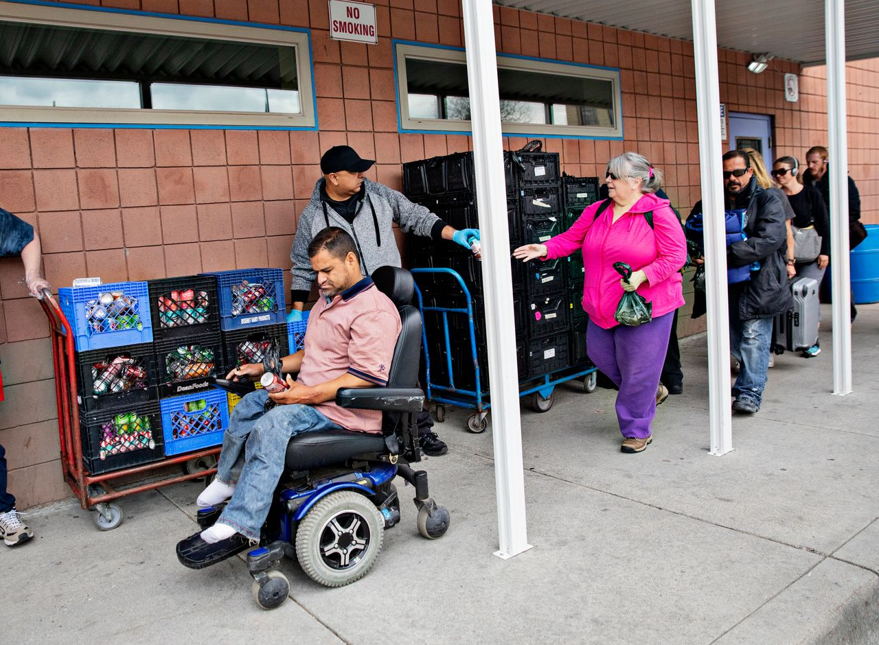 Over a hundred people move through the line to receive a bagged lunch outside of the St. Vincent De Paul Dining Hall on April 30, 2019, in Salt Lake City.