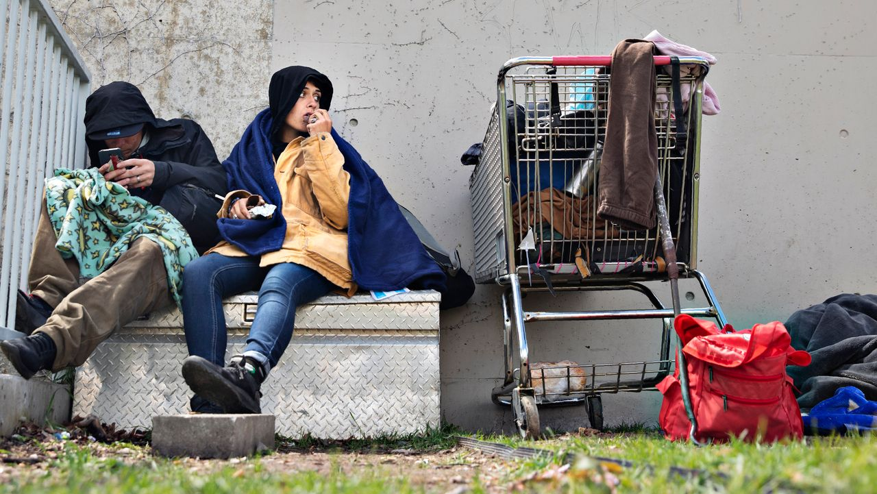 John and a woman, both homeless, sit in a courtyard at Library Square where they try and sleep most nights on May 1, 2019, in downtown Salt Lake City.
