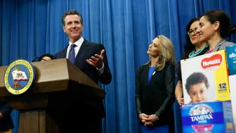 """Gov. Gavin Newsom discusses a proposal to eliminate the state sales tax on tampons and diapers in his upcoming state budget during a news conference, Tuesday, May 7, 2019, in Sacramento, Calif. The tax cuts are part of a """"parents' agenda"""" Newsom is pursuing, and he plans to unveil a revised state budget later this week. Newsom was, accompanied by his wife, first partner Jennifer Siebel Newsom, second from left, Southern California Democratic Assembly members Lorena Gonzalez, third from left, and Monique Limon, right, (AP Photo/Rich Pedroncelli)"""