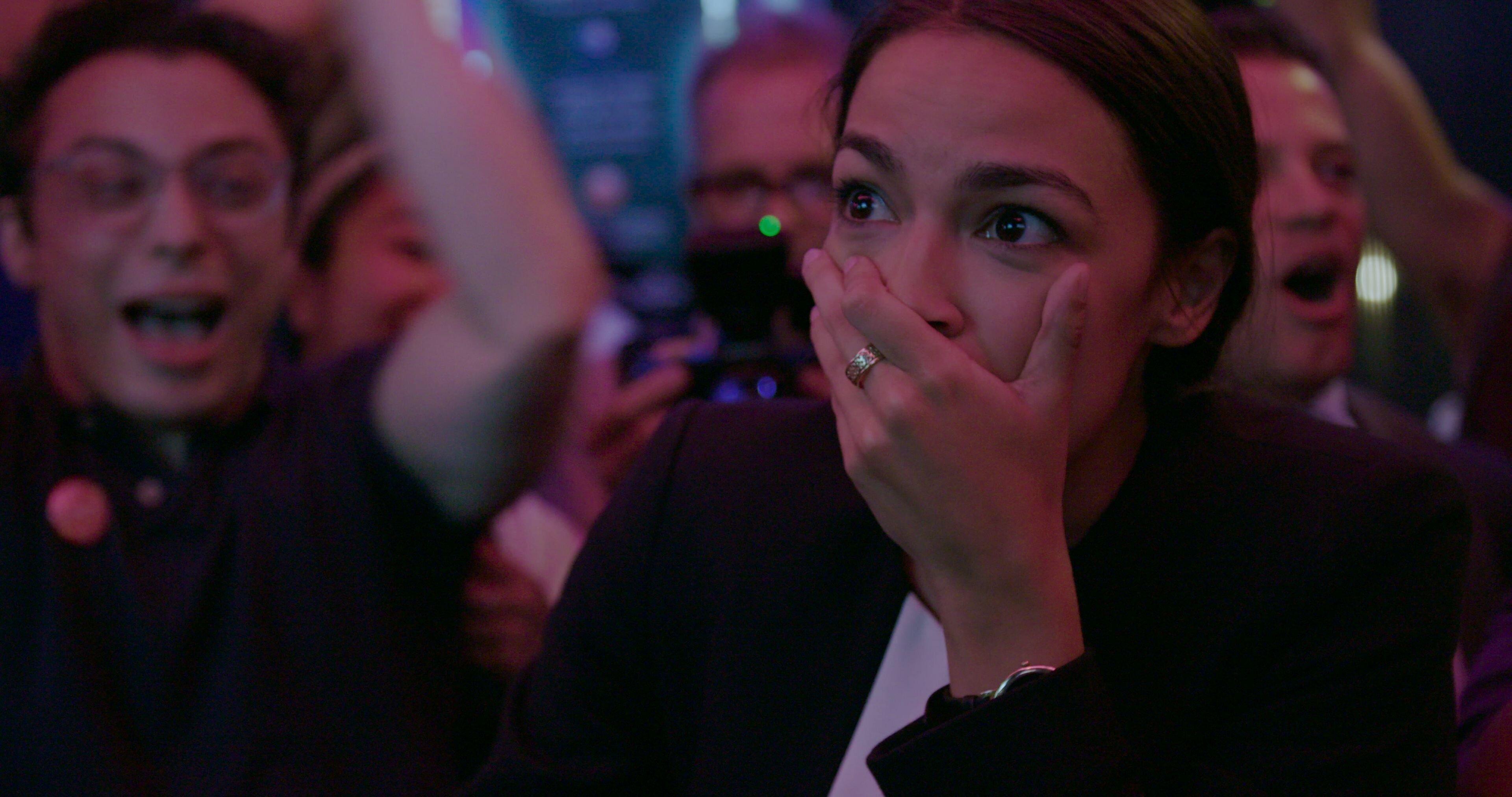 Alexandria Ocasio-Cortez com cara de surpresa ao vencer as primárias do Partido Democrata em 2018,...