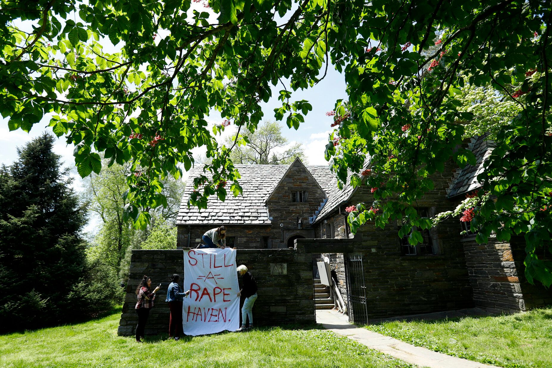 Swarthmore College students hang a banner near the Phi Psi fraternity house during a sit-in at the suburban Philadephia campu