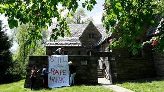 Swarthmore College students hang a banner near the Phi Psi fraternity house during a sit-in, Monday, April 29, 2019, in Swarthmore, Pa. Students at the suburban Philadelphia college have occupied the on-campus fraternity house in an effort to get it shut down after documents allegedly belonging to Phi Psi surfaced this month containing derogatory comments about women and the LGBTQ community and jokes about sexual assault. (AP Photo)