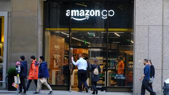 FILE - In this Jan. 30, 2019, file photo people walk past and into an Amazon Go store in San Francisco. An Amazon Go store opening Tuesday, May 7, 2019, in New York, will be the first of its kind to accept cash. (AP Photo/Eric Risberg, File)