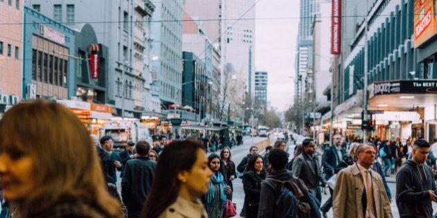 Commuters outside Flinders Street Station cross the road on the croner of flinders street and Elizabeth...