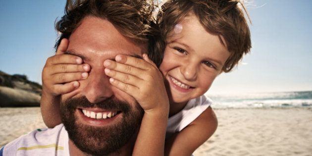 Boy (4-5) with hand over fathers eyes, close