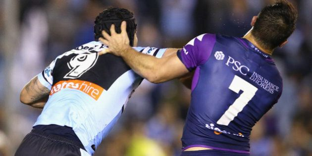 SYDNEY, AUSTRALIA - AUGUST 17: Michael Ennis of the Sharks pushes away Cooper Cronk of the Storm as they...