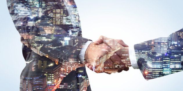 Double exposure of two business men shaking hands with a city view of the financial district at night.