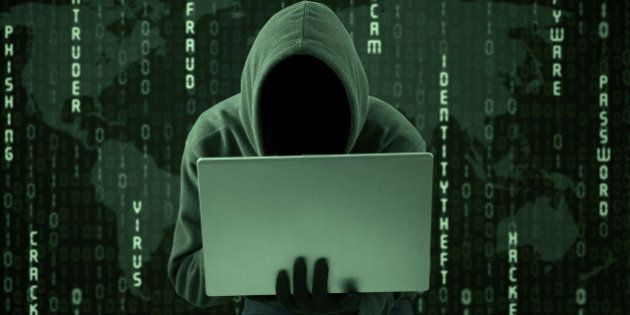 Hacker typing on a laptop with binary code