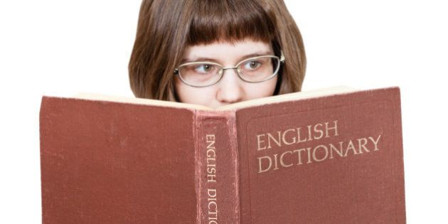 girl with glasses reads big English Dictionary book isolated on white