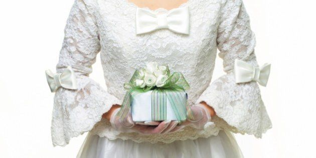 Photography of a bride holding a present in hands, Front