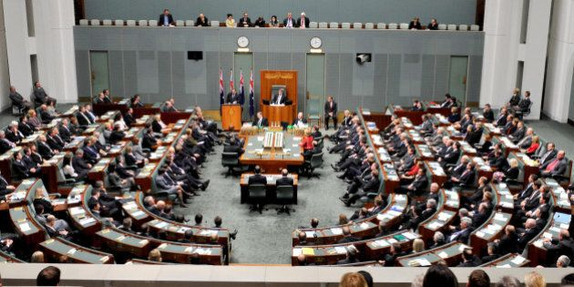 New Zealand's Prime Minister John Key, standing before flags, addresses a joint sitting of the Australian...
