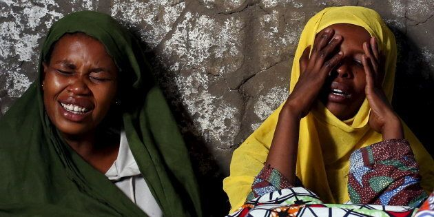 Two women weep and pray for their relative Ndayizeye Janvier Abdul, 36, who was killed by the Imbonerakure,...