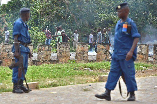 Burundian police look on as members of the Imbonerakure, armed with sticks, destroy barricades erected...
