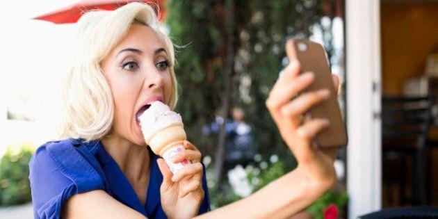USA, California, Costa Mesa, Woman photographing herself with ice-cream