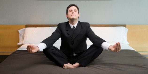 Businessman meditating on the bed in a hotel