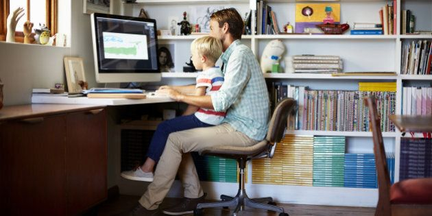 Boy sitting on father's lap at computer desk in living room