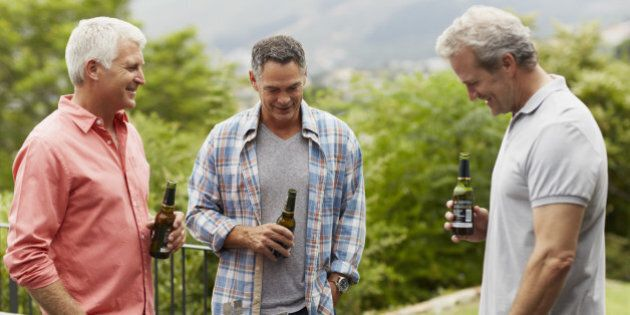 Happy mature male friends having beer while looking at barbecue in yard