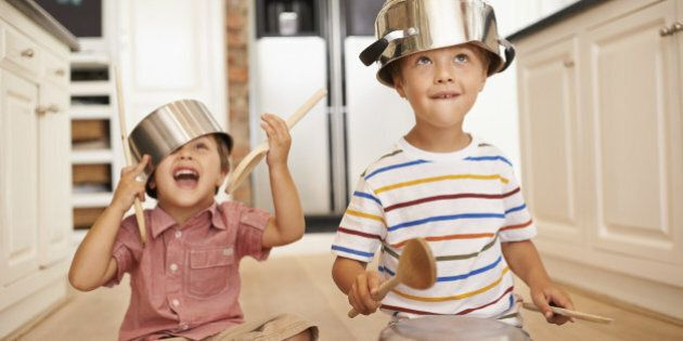 Two young boys sitting on the kitchen floor playing with pots and
