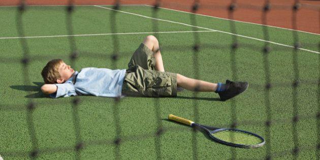 Boy lying on tennis