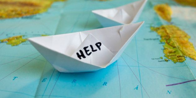 White paper boat onto world map with 'Help' sign on