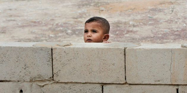 A Syrian boy peeks from behind a wall near a mobile clinic at a refugee camp in the southern town of...