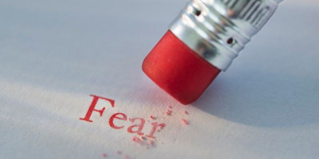 Studio shot of pencil erasing the word fear from piece of
