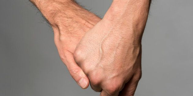Two gay men holding hands on gray background