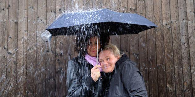 Two women under one umbrella