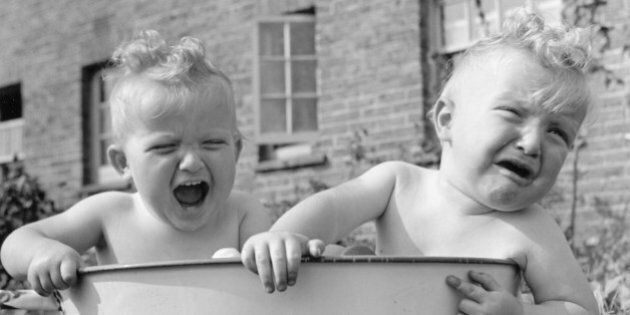 Young twins Martin and Peter Thompson, who took first prize at a local baby show for the second year in succession, sharing a bath in the garden of their Kent home.