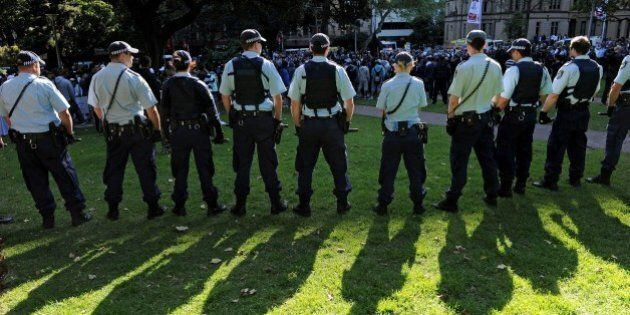 Police stand guard as people protest at Hyde Park in Sydney on September 15, 2012, as a wave of unrest against a film that mocks Islam spread to Australia, bringing hundreds out to demonstrate. Furious protests targeting symbols of US influence flared in cities across the Muslim world on September 14 in retaliation for a crude film made in the United States by a right-wing Christian group that ridicules the Prophet Mohammed. AFP PHOTO / Greg WOOD        (Photo credit should read GREG WOOD/AFP/GettyImages)