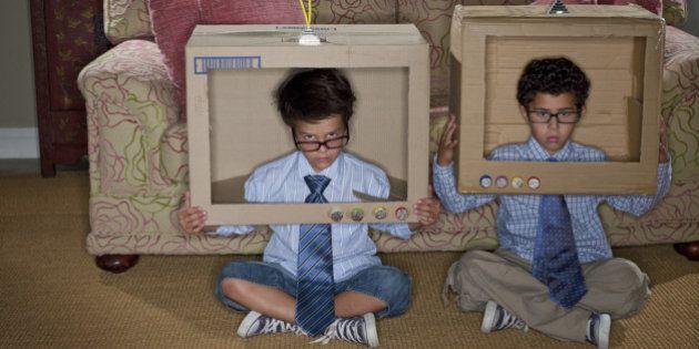 Boys dressed as businessmen sitting in cardboard