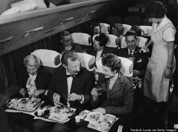 Interior view of a commercial passenger plane shows, in the foreground, a couple as they enjoy their meal next to a smiling elderly woman, while behind them, a flight attendant pours a glass of wine for a man who sits next to a couple who toast each other with full glasses, 1950s. (Photo by Frederic Lewis/Getty Images)