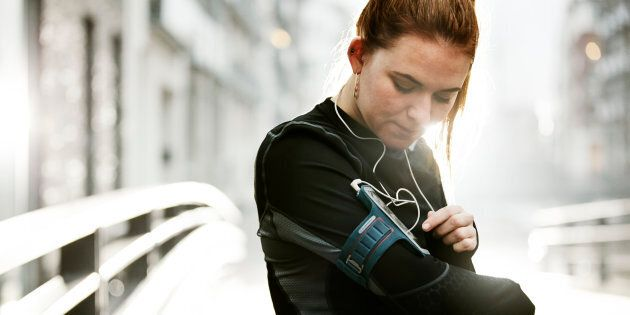 female runner preparing in urban invironment, checking the music at her