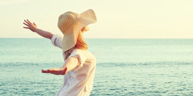 Happy beauty woman in hat is back opened his hands, relaxes and enjoys the sunset over the sea on the