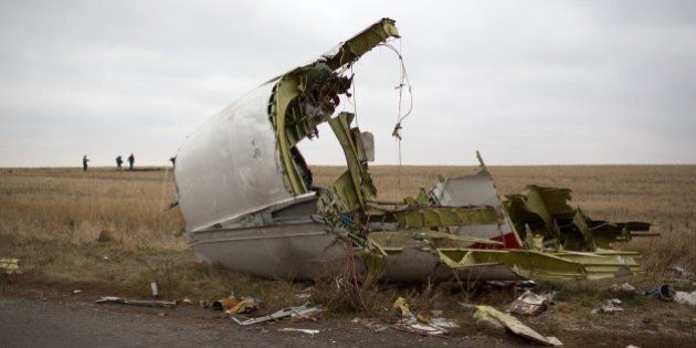 Journalists walk behind parts of the Malaysia Airlines plane Flight MH17 as Dutch investigators (unseen)...
