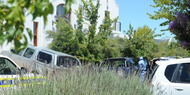 Police forensic investigators at De Zalze Golf Estate where three family members were hacked to death.