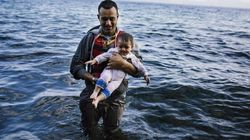 Innocents Of The Refugee Crisis Are Carried Ashore By Desperate Parents, Swaddled Against The