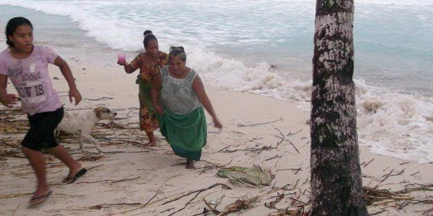 KIRIBATI - MARCH 13:  In this handout image provided by Plan International Australia, people move away from the beach March 13, 2015 on the island of Kiribati. Cyclone Pam is pounding South Pacific islands with hurricane force winds, huge ocean swells and flash flooding. (Photo by Plan International Australia via Getty Images)