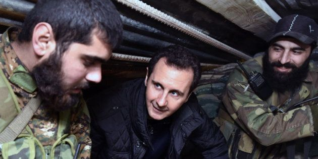 FILE -- In this Wednesday, Dec. 31, 2014, file photo released by the Syrian official news agency SANA, Syrian President Bashar Assad, center, speaks with Syrian troops during his visit to the front line in the eastern Damascus district of Jobar, Syria. A Russian initiative to host peace talks this month between the Syrian government and its opponents appears to be unraveling, as prominent Syrian opposition figures shun the planned negotiations over concerns that the framework is flawed and holds little chance of success. (AP Photo/SANA, File)