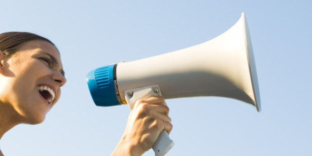 Woman shouting into megaphone, low angle view,