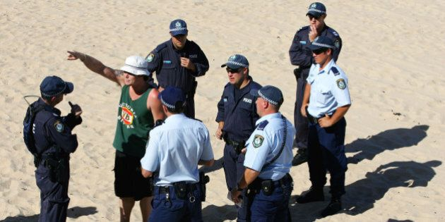 Police question a man on Cronulla Beach in Sydney, Australia, Sunday, Dec. 18, 2005. Cronulla is one...