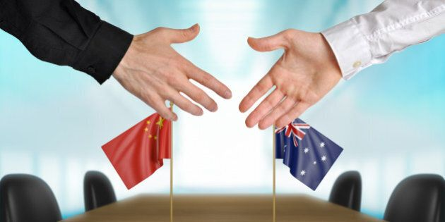 Two diplomats from China and Australia extending their hands for a handshake on an agreement between...