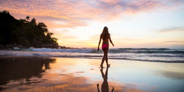 A woman walking in the sand on a tropical beach at