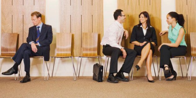 Business people ignoring businessman in waiting