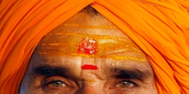 A Sadhu, or Hindu holy man, his face smeared with turmeric and vermilion paste, looks on at the Sangam,...