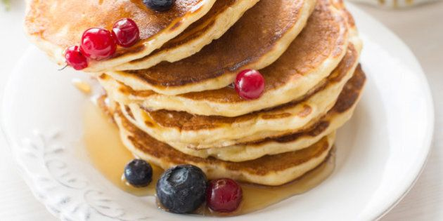 Stack of pancakes topped with blueberries, cranberries and honey on white plate on white table. Vertical breakfast image