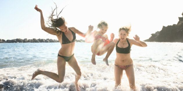 Three girls jumping on wave in