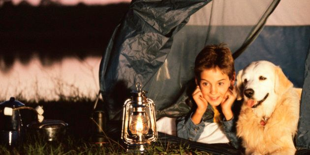 Boy lying in a tent with his
