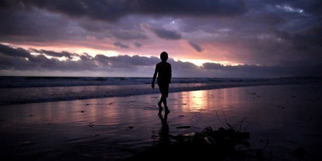 A young boy walks at sunset on the beach of Kerema, papua New Guinea, on September 9, 2014. AFP PHOTO...